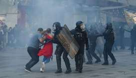 People run among tear gas on the Champs Elysees avenue during an anti-government demonstration calle