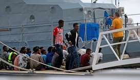 A police officer speaks to rescued migrants after they arrived on an Armed Forces of Malta patrol bo