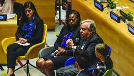 UN Secretary General Antonio Guterres speaks next to the youth climate activists at the event, (left
