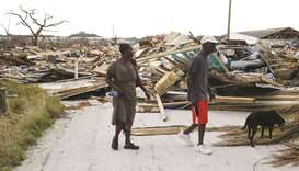People walk among debris at the Mudd neighbourhood, devastated after Hurricane Dorian hit.