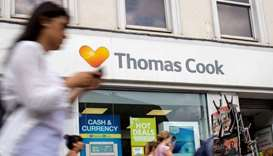 Pedestrians are pictured walking past a branch of a Thomas Cook travel agent's shop