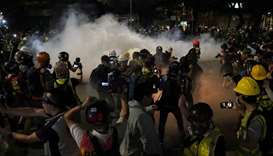 Members of the media react to the tear gas fired by the police in Tuen Mun, Hong Kong
