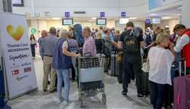People line up in front of a counter of Thomas Cook at the Heraklion airport on the island of Crete,