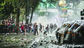 Indonesian police use shields to protect from rocks thrown by student protesters rallying against di