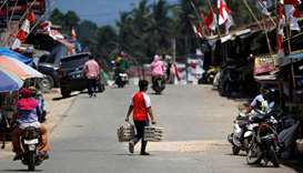 A man carries eggs as he crosses a street at a Sepaku market in North Penajam Paser regency, East Ka