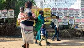 Pedestrians walk past signs of the various daily newspapers on the streets of Harare on the first da