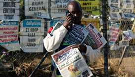 A vendor sells the various daily newspapers on the streets of Harare on the first day of a period of