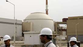 Iran technicians walk outside the building housing the reactor of Bushehr nuclear power plant