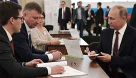 Russian president Vladimir Putin (R) arrives prior to casting his vote at a polling station during t