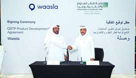 Waasla founder and CEO Ali al-Marri (L) and QSTP executive director Yosouf Abdulrahman Saleh shake h