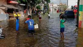 Residents make their way through a flood street after last week's heavy rains in Keur Massar, Senega