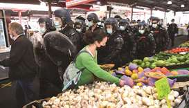 A woman continues to shop for vegetables as riot police clear Melbourne's Queen Victoria Market of a