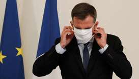 French Health Minister Olivier Veran puts on his protective mask after addresses media representativ