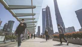 Pedestrians wearing protective masks walk through the Lujiazui Financial District in Shanghai. Globa
