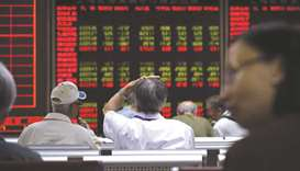Investors look at screens showing stock market movements at a securities company in Beijing. The Com
