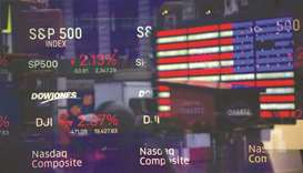 Monitors displaying stock market information are seen through the window of the Nasdaq MarketSite in