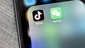 The WeChat and TikTok app icons are displayed on a smartphone in an arranged photograph taken in Arl