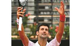 Serbia's Novak Djokovic pretends cheering the crowd in an empty central court, after winning his qua