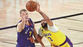 Denver Nuggets forward Mason Plumlee and Los Angeles Lakers forward Anthony Davis (right) reach for