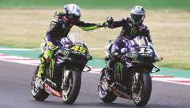 Monster Energy Yamaha's Maverick Vinales (R) celebrates qualifying in pole position with teammate Ya