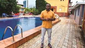 Eric Moussambani standing next to a 12m long small swimming pool, very similar to the small one he u
