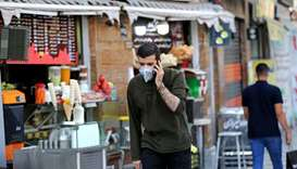 A man, wearing a protective mask due to the Covid-19 pandemic, walks past shops in Valiasr square in