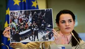 Belarusian opposition leader Sviatlana Tsikhanouskaya holds a picture as she speaks to the members o