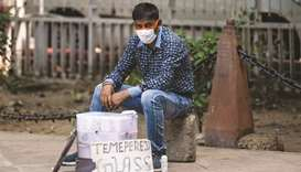 A vendor wearing a face mask as a preventive measure against the Covid-19 coronavirus waits for cust