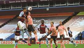 Aston Villa's English defender Ezri Konsa (left) jumps to head the ball over Sheffield United's Iris