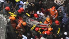Rescue workers search for survivors in the rubble of a collapsed three-storey residential building i