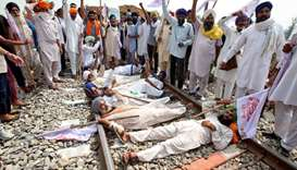 Farmers shout slogans as they block a railway track during a protest against farm bills passed by In