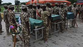 Nigerian soldiers stand on attention during the funeral of the soldiers killed in the attack on vehi
