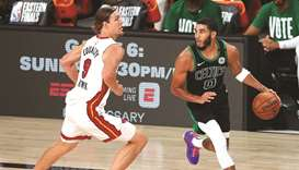 Boston Celtics forward Jayson Tatum (right) moves the ball against Miami Heat forward Kelly Olynyk d