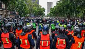 Demonstrators confront riot police in Mexico City yesterday during a march for the sixth anniversary