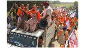 Farmers shout slogans as they arrive to block railway tracks during a protest.