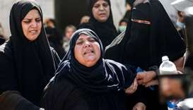 Mourners comfort the mother of two Palestinian fishermen who were shot at sea, during their funeral