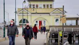 Walkers wear protective face masks at St Kilda pier in Melbourne.