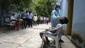 Residents stand in a queue to register their names as a health worker (R) wearing Personal Protectiv