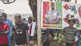 Supporters of junta leader, Colonel Mamady Doumbouya, stand around a poster of him at the People's P