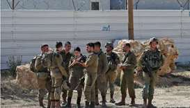 Members of Israeli security forces stand guard near the Palestinian city of Bethlehem in the occupie