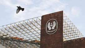A bird flies past a logo of Life Insurance Corporation of India at one of its offices in New Delhi (