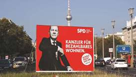 Vehicles pass by an election poster showing Olaf Scholz, German Minister of Finance and top candidat
