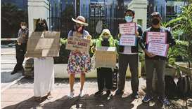 Environmental activists wearing protective masks hold placards outside the Central Jakarta Court fol