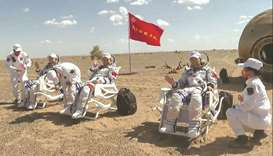 Chinese astronauts Tang Hongbo, Nie Haisheng and Liu Boming being inspected by medical personnel out