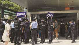 Police officers look at people gathering at the Evergrande headquarters in Shenzhen. China injected