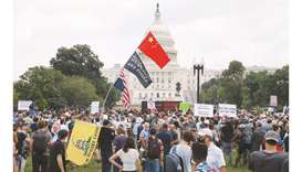 People hold signs as they gather in front of the US Capitol during the rally.