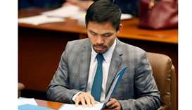 Philippine Senator and boxing champion Manny Pacquiao reads his briefing materials as he prepares fo