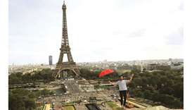 French highliner Nathan Paulin holds an umbrella yesterday as he performs, for the second time, on a