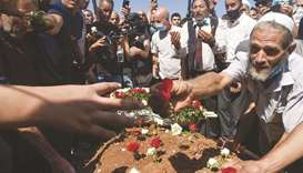 Algerians place roses on the tomb of former president Abdelaziz Bouteflika during his funeral at the