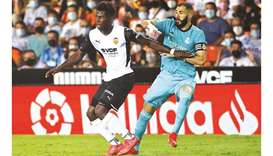 Real Madrid's Karim Benzema (right) vies for the ball with Valencia's Yunus Musah during the La Liga
